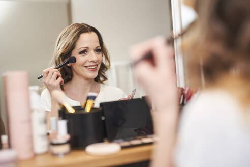 Frau mit Make-up Pinsel vor Spiegel. München, Deutschland - PNEF01663