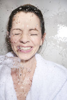 Water splashing into face of happy woman in bathrobe - PNEF01681