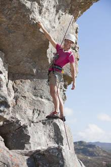 Portrait of confident female rock climber ascending rock face - JUIF01454