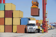 Crane loading cargo container onto lorry at commercial dock - JUIF01472