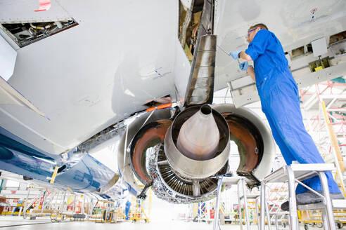 Engineer working under wing of passenger jet in hangar - JUIF01502