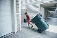 Mixed race boy pulling trash can in driveway - BLEF07223