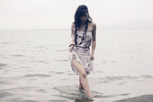Caucasian woman wading in water on beach - BLEF07262