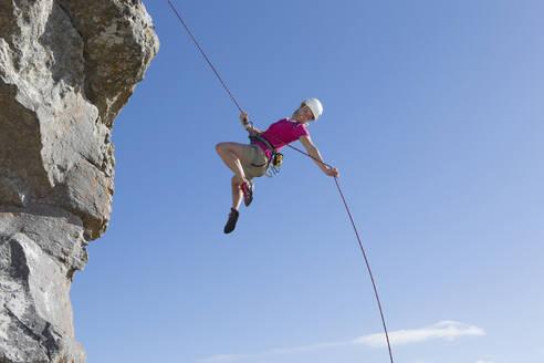Female rock climber abseiling down rock face - JUIF01512