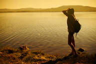 Caucasian woman standing by still rural lake - BLEF07274
