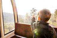 Caucasian boy looking out tram window - BLEF07337