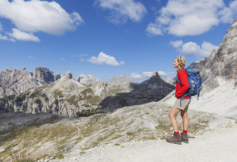 Female hiker looking at view, Tre Cime di Lavaredo Area, Nature Park Tre Cime, Unesco World Heritage Natural Site, Sexten Dolomites, Italy - GWF06116