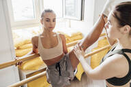 Fitness instructor practicing barre workout with young woman in gym - VPIF01265