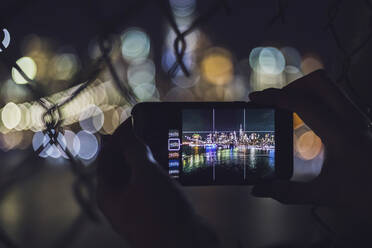Close-up of woman taking smartphone picture of skyline at night, Manhattan, New York City, USA - MMAF01053