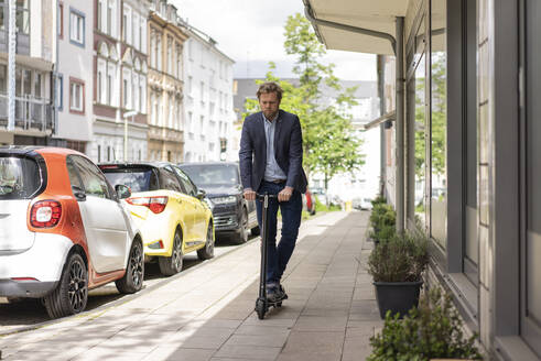 Businessman riding E-Scooter on pavement - JOSF03279