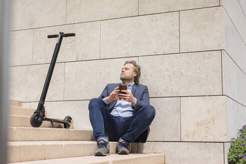 Businessman with E-Scooter and smartphone sitting on steps relaxing - JOSF03288