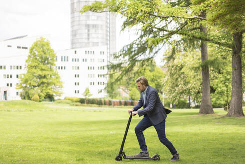 Businessman using E-Scooter on a meadow in city park, Essen, Germany - JOSF03303