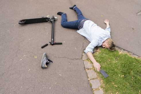 Accident victim lying on road besides E-Scooter and smartphone - JOSF03309