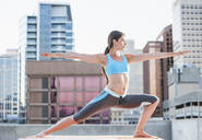 Caucasian woman practicing yoga on urban rooftop - BLEF07426