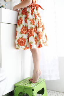 Mixed race girl standing on stool on tiptoe - BLEF07432