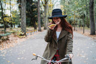 Young woman with long red hair on bicycle looking at smartphone in autumn park, Florence, Tuscany, Italy - CUF51428