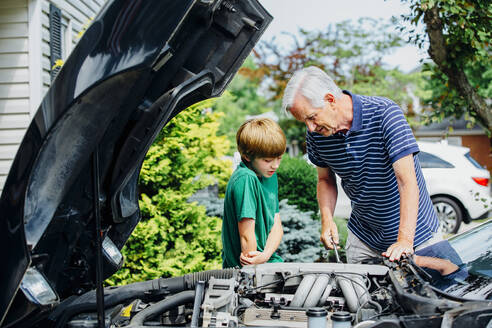 Caucasian grandfather and grandson working on car in driveway - BLEF07547