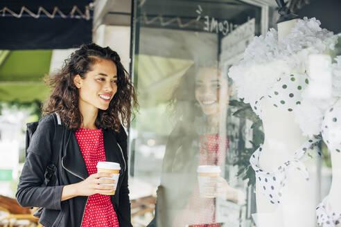Mixed race woman window shopping outside store - BLEF07565