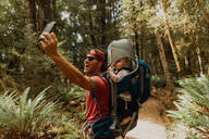 Father with baby taking selfie in forest, Queenstown, Canterbury, New Zealand - ISF21509