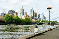 Man sitting at Yarra river looking towards skyscrapers in Melbourne, Victoria, Australia - KIJF02493