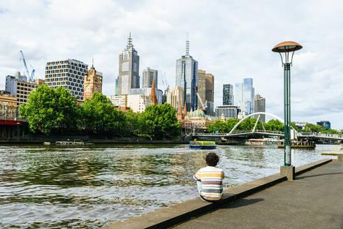 Australia, Melbourne, man sitting by Yarra river looking towards skyscrapers in Melbourne. - KIJF02493