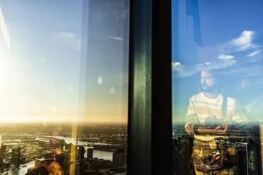Reflection of man in glass with cityscape of Melbourne, Victoria, Australia - KIJF02496