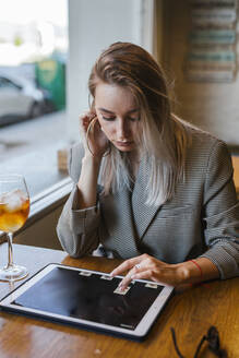 Young businesswoman using tablet in a bar - LJF00149