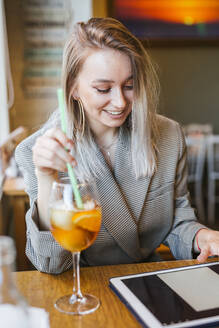 Young businesswoman using tablet in a bar - LJF00152