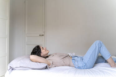 Happy young woman lying on bed with closed eyes - AFVF03301