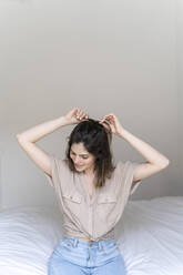 Young woman sitting on bed doing her hair - AFVF03307