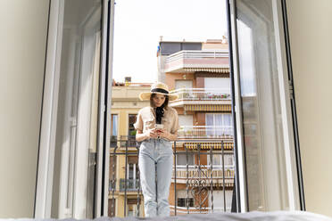 Young woman on balcony in the city using cell phone - AFVF03313