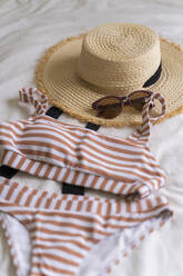 Bikini and straw hat lying on bed - AFVF03322