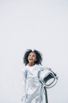 Portrait of amazed little girl wearing space suit in front of white background looking up - JCMF00064