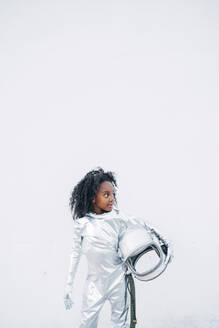 Little girl wearing space suit in front of white background looking around - JCMF00067