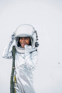 Portrait of laughing little girl wearing space suit and space hat in front of white background - JCMF00070