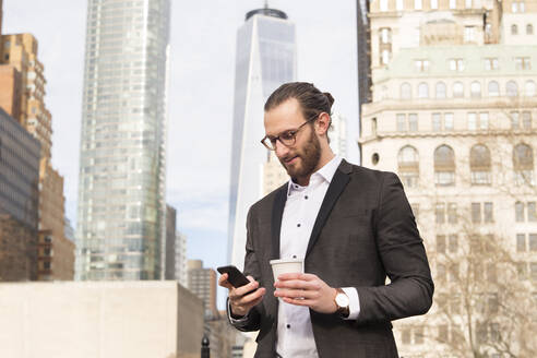 Bearded young businessman with coffee to go looking at cell phone, New York City, USA - MFRF01303