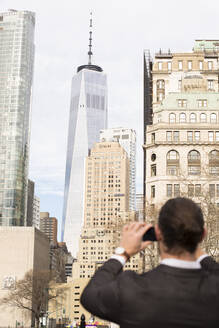 Back view of man taking pictures with smartphone, New York City, USA - MFRF01306