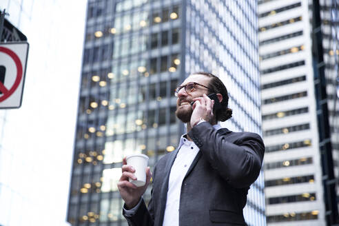 Happy young businessman with coffee to go on the phone, New York City, USA - MFRF01312