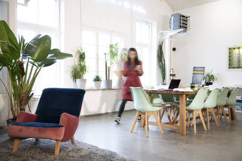Woman moving in modern office - FKF03356