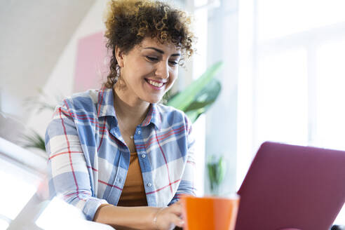 Smiling woman using laptop in office - FKF03362