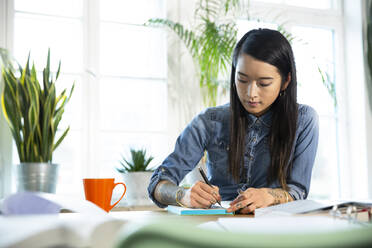 Woman working at table in office taking notes - FKF03404
