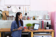Woman with laptop in office kitchen - FKF03416