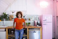 Portrait of smiling woman standing in office kitchen - FKF03425