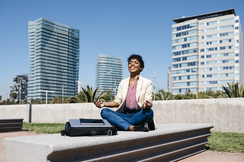 Businesswoman sitting on bench and meditating - JRFF03296