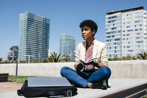 Spain, Barcelona. Afro business girl taking notes in a notebook sitting on a city bench. - JRFF03299