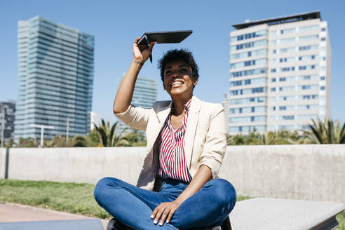 Spain, Barcelona. Afro girl working sitting on a city bench getting out of the sun with a notebook one sunny day - JRFF03305