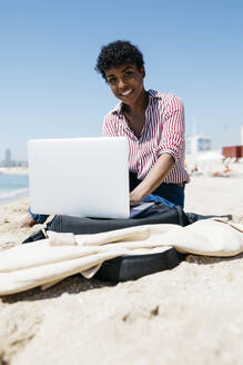 Spain, Barcelona. Afro working girl sitting on the sand of the beach while working with the laptop - JRFF03320