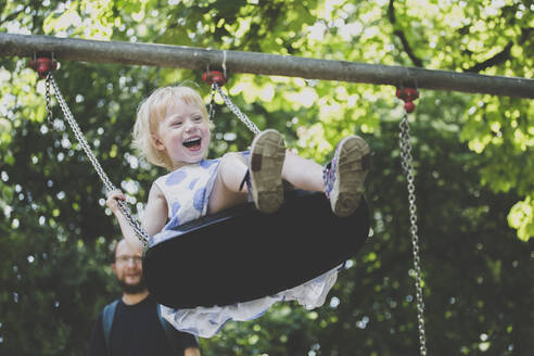 Portrait of happy ltiitle girl on a swing - IHF00141