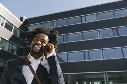 Smiling businessman talking on cell phone outside office in the city - AHSF00526