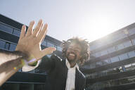 Happy businessman giving high-five outside office - AHSF00541